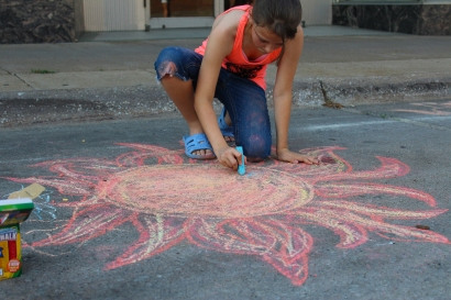 Muscatine Second Saturday: Child drawing with chalk